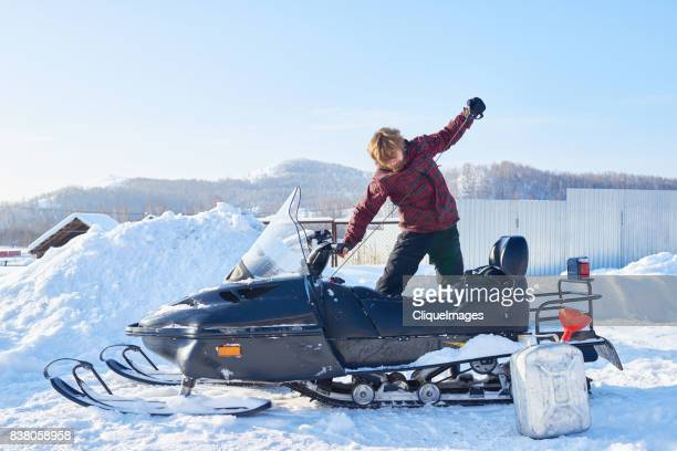 man starting snowmobile - cliqueimages stock pictures, royalty-free photos & images