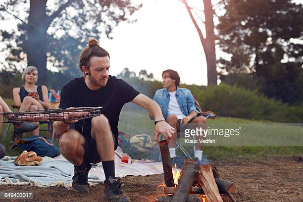 Man starting up bonfire at campsite
