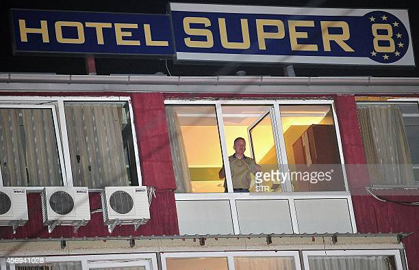 A man staying at the hotel where a British national displaying Ebolalike symptoms was also staying looks out from a window as the hotel was sealed...