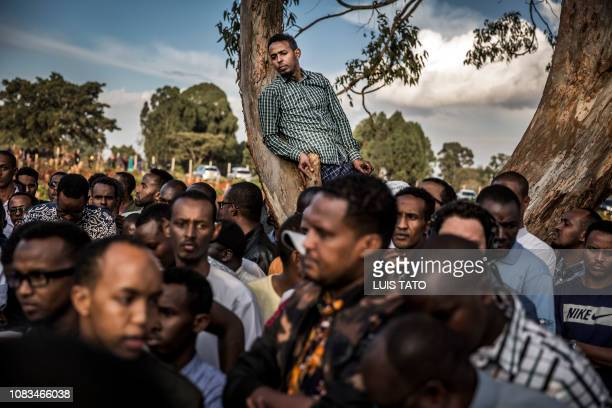 Man stays on a tree during the burial ceremony of Abdalla Mohamed Dahir and Feisal Ahmed who were killed the previous day in an attack during his...