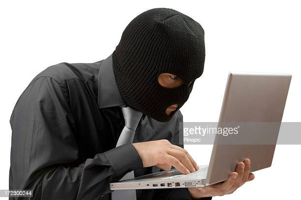 man stealing data from a laptop isolated - balaclava stock pictures, royalty-free photos & images