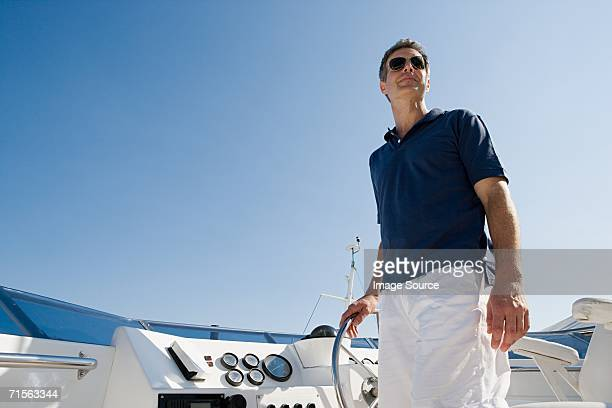 man steering a yacht - yacht stock pictures, royalty-free photos & images
