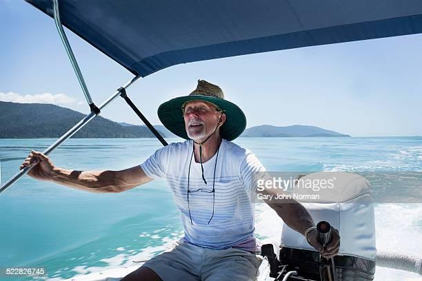 Man steering motor boat or tinnie.