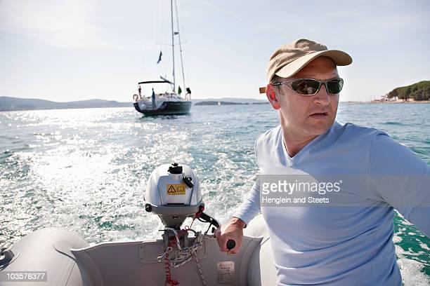 Man steering yacht dinghy