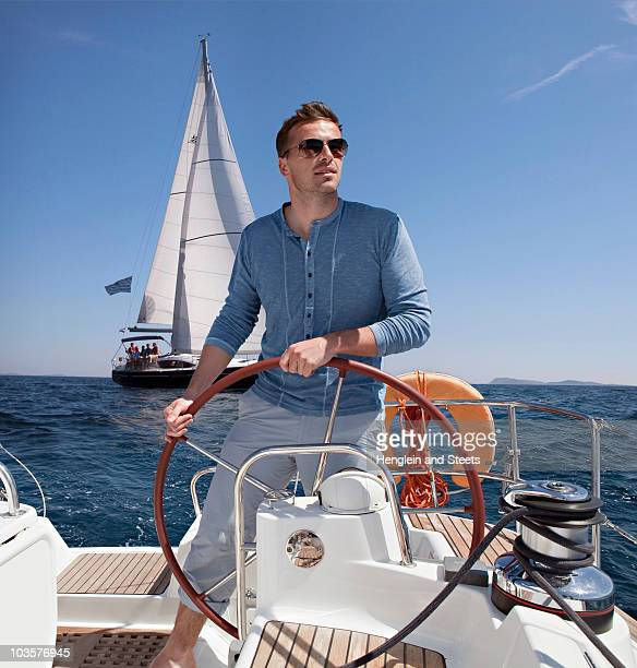Man steering yacht
