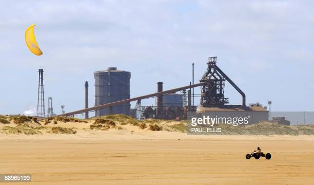 A man steers a kite buggy on the beach near a Corus steelworks at Redcar in northeast England on May 11 2009 Nearly 2000 jobs are at risk at one of...