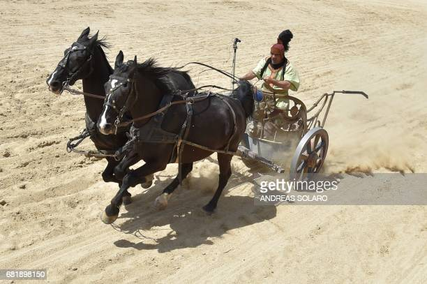 A man steers a Roman chariot drawn by two horses during a race against Ferrari driver Fabio Barone and his Ferrari 458 Italia on May 11 2017 on Ben...