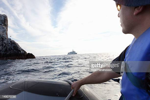 A man steers an inflatable boat towards a ship
