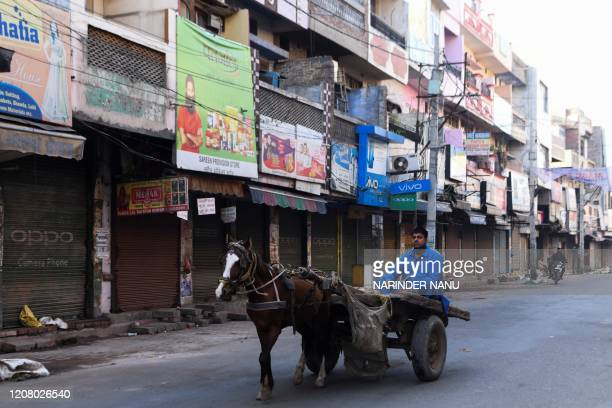 TOPSHOT A man steers his horsecart past by closed shops after the authorities imposed a lockdown as a preventive measure against the COVID19 novel...