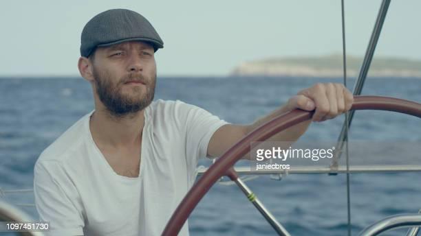 ヨットを操縦する男 - チームキャプテン ストックフォトと画像