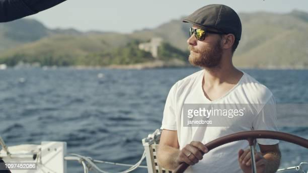 hombre dirige el yate - capitán del equipo fotografías e imágenes de stock