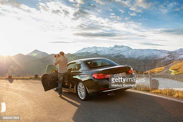 man stepping out of his car to take a picture. - ein mann allein stock-fotos und bilder