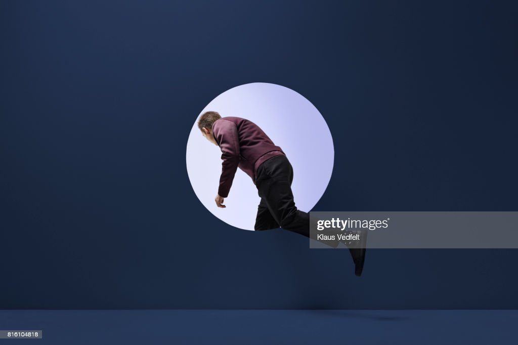 Man stepping threw round opening in coloured wall : Stock Photo