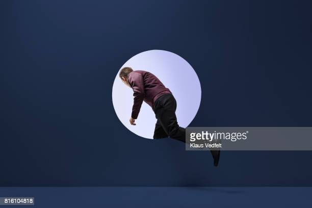 man stepping threw round opening in coloured wall - curiosity stock pictures, royalty-free photos & images