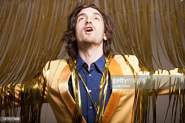 A man stepping through a golden curtain