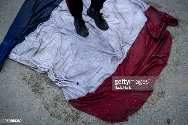 Man steps on the national flag of France during a protest against French President Emmanuel Macron on October 29, 2020 in Tripoli, Libya. Muslims...