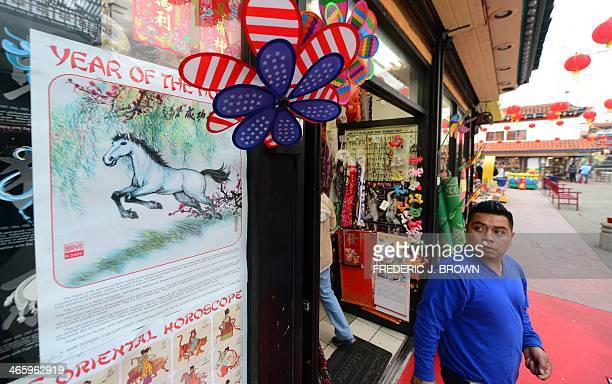 A man steps out of a shop selling curios and trinkets looking toward a Year of the Horse on the shopfront window in Chinatown's Central Plaza in Los...
