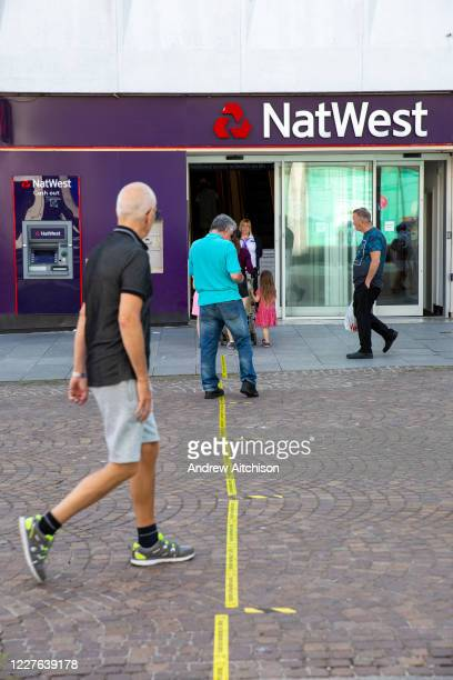 Man steps over the 2 metre social distancing advice line taped to the floor outside NatWest bank on the15th of June 2020 in Folkestone, United...