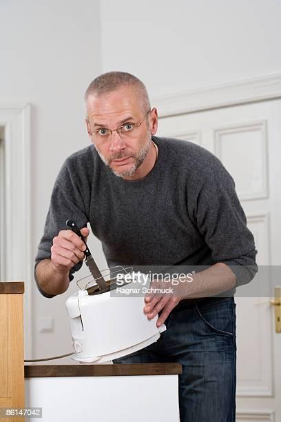 a man sticking a knife in a toaster - achtlos stock-fotos und bilder