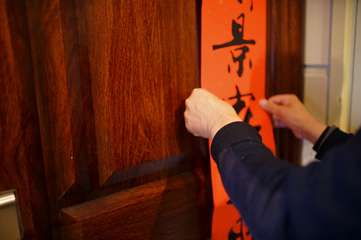 A man sticking Chinese Couplets of greeting on the door for traditional Chinese New year. - gettyimageskorea