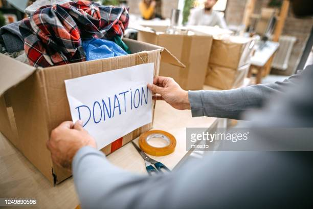 man sticking donation label to carton box - giving tuesday stock pictures, royalty-free photos & images