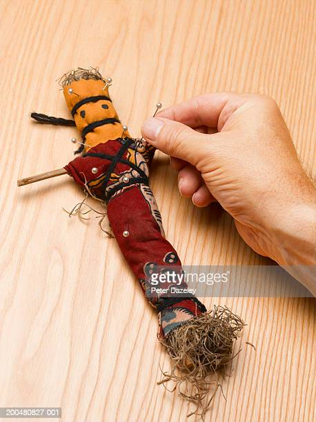 Man sticking pin in vodoo doll, close-up of hand