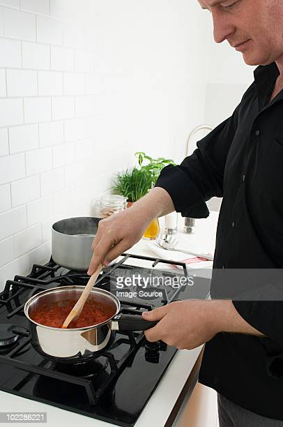 Man stirring sauce in saucepan