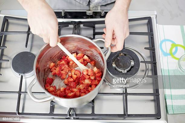 Man stirring strawberries on gas stove