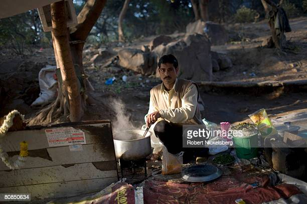 A man stirs a pot cooking lunch in an open air restaurant along the metro route in the Jhandewalan district of New Delhi India February 21 2008...