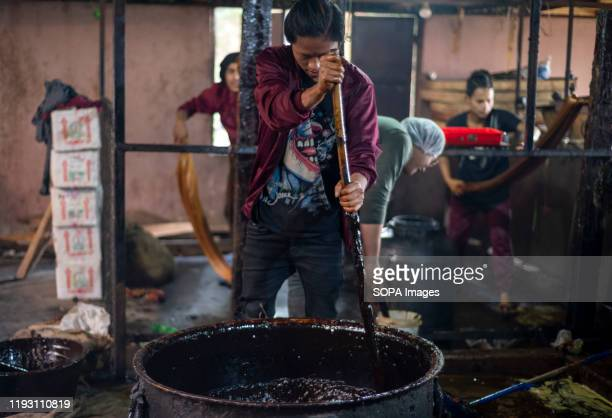 A man stirs boiled molasses during the preparation process of chaku for the Maghe Sankranti festival Chaku Molasses is usually prepared and consumed...