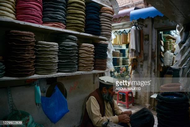 Man stitches Chitrali woolen caps, which are popular among the local people particularly during the winter months, at a bazaar in Peshawar on...