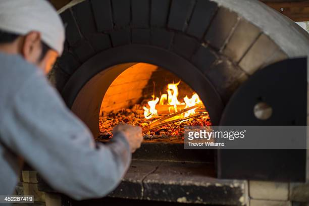 A man stoking the fire in a stone oven