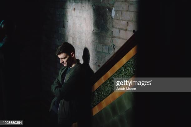 Man stood against wall