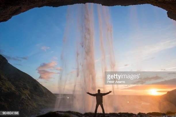 Man stood behind Seljalandsfoss waterfall, Iceland