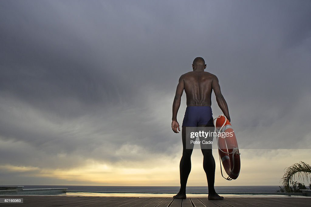 Man stood by pool holding life ring : Stock Photo
