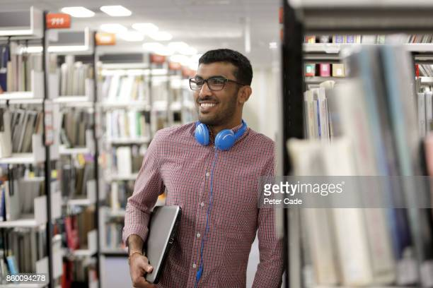 man stood in library with book under arm - person in education stock pictures, royalty-free photos & images