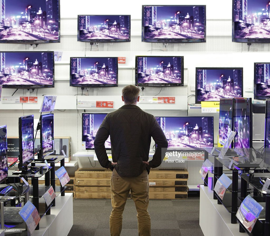 Man stood in shop surrounded by televisions : Stock Photo