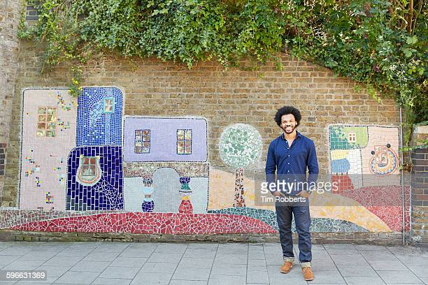 Man stood infront of art wall.