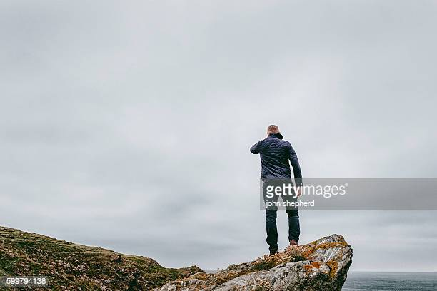 man stood on a cliff top, grey dramtic foreboding sky - calm before the storm stock pictures, royalty-free photos & images