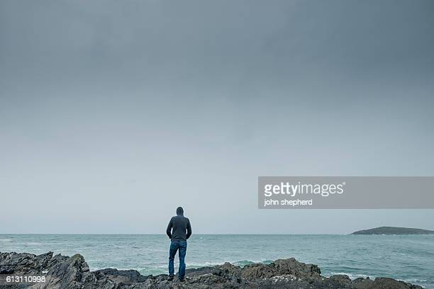 Man stood on rocks on the shoreline in gloomy weather.