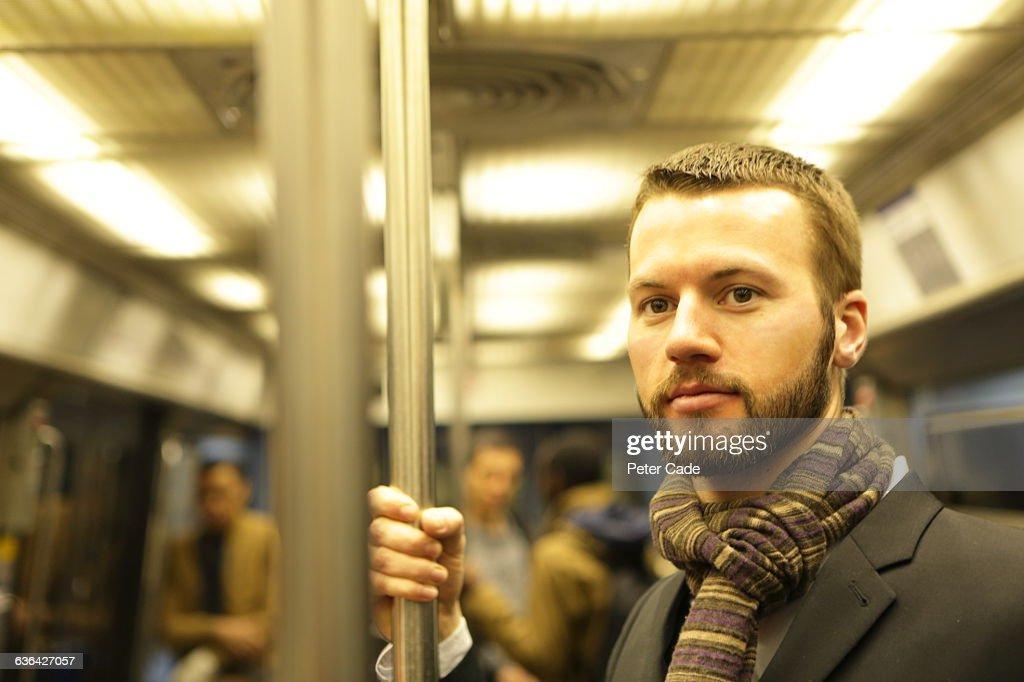 Man stood on underground train : Stock Photo