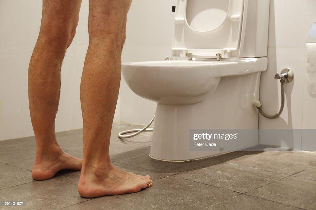 Man stood over toilet : Stock Photo