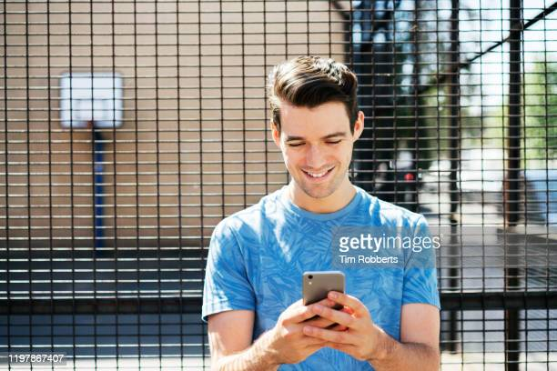 man stood using smart phone - reading stock pictures, royalty-free photos & images