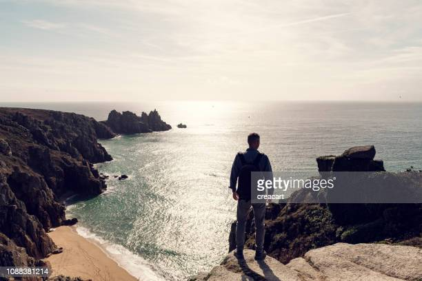 Man stood with backpack backlit in strong Autumn sunshine above Pedn Vounder Beach, South Cornwall on a late September day.
