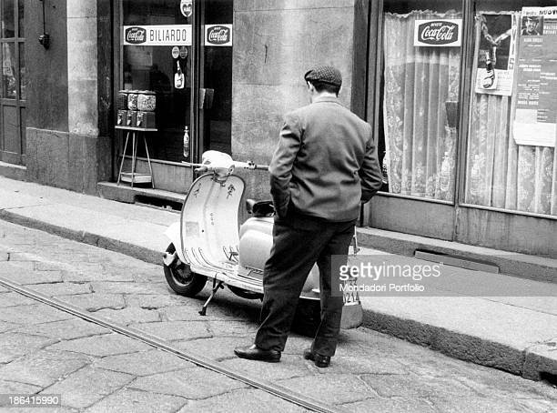 A man stopping to observe a Vespa parked outside a bar Milan April 1963