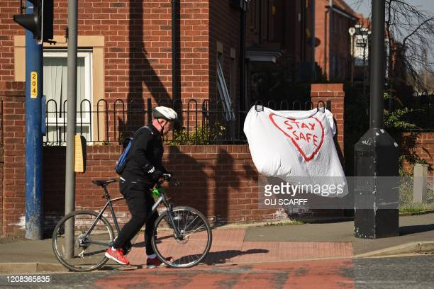 "Man stops his bicycle beside a slogan asking people to ""stay safe"", written on a bed sheet attached to some railings in Manchester, north-west..."