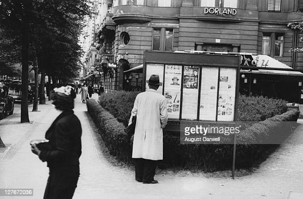 A man stops on a Berlin street corner to read the newspaper pasted on a red billboard June 1939 The paper is Der Sturmer the infamously antiSemitic...