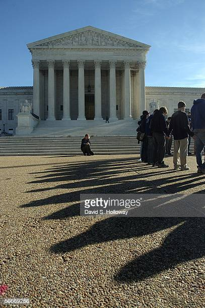 A man stops on the sidewalk to kneel behind the March for Life prayer vigil in front of the Supreme court building on January 22 2006 in Washington...