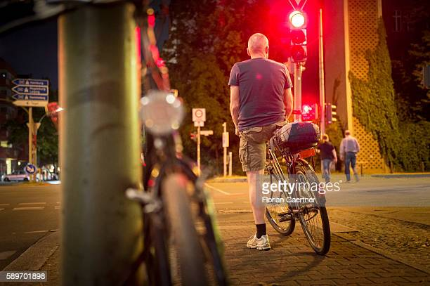 A man stops riding her bike because of the red traffic light on August 09 2016 in Berlin Germany