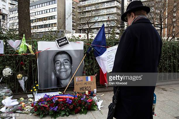 A man stops to look at a tribute to murdered police officer Ahmed Merabet ahead of his funeral on January 13 2015 in Bobigny France All three police...